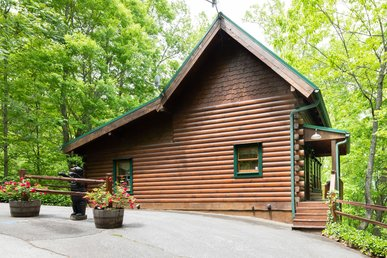 Charming cabin with wrap-around porch, pool access, and hot tub